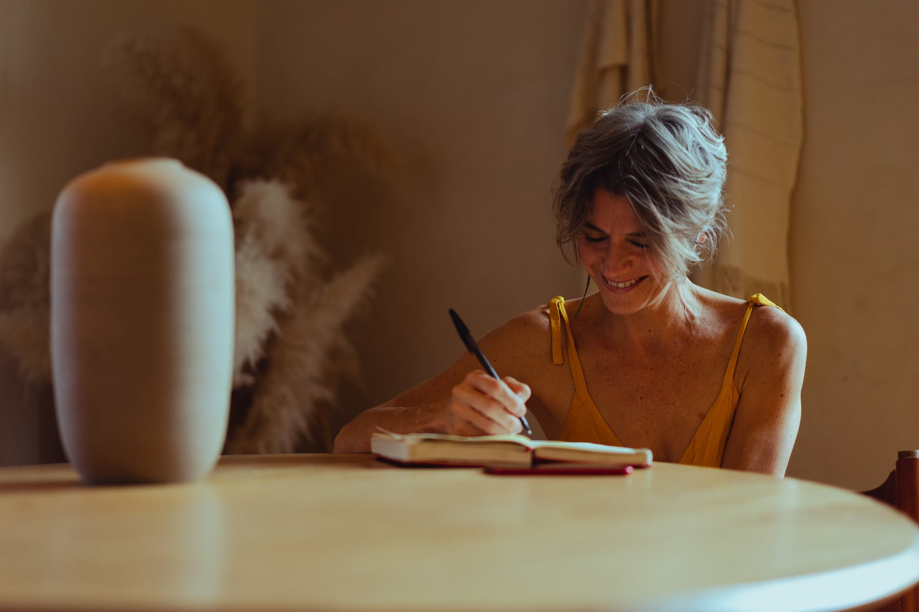 elderly woman writing her diary while smiling